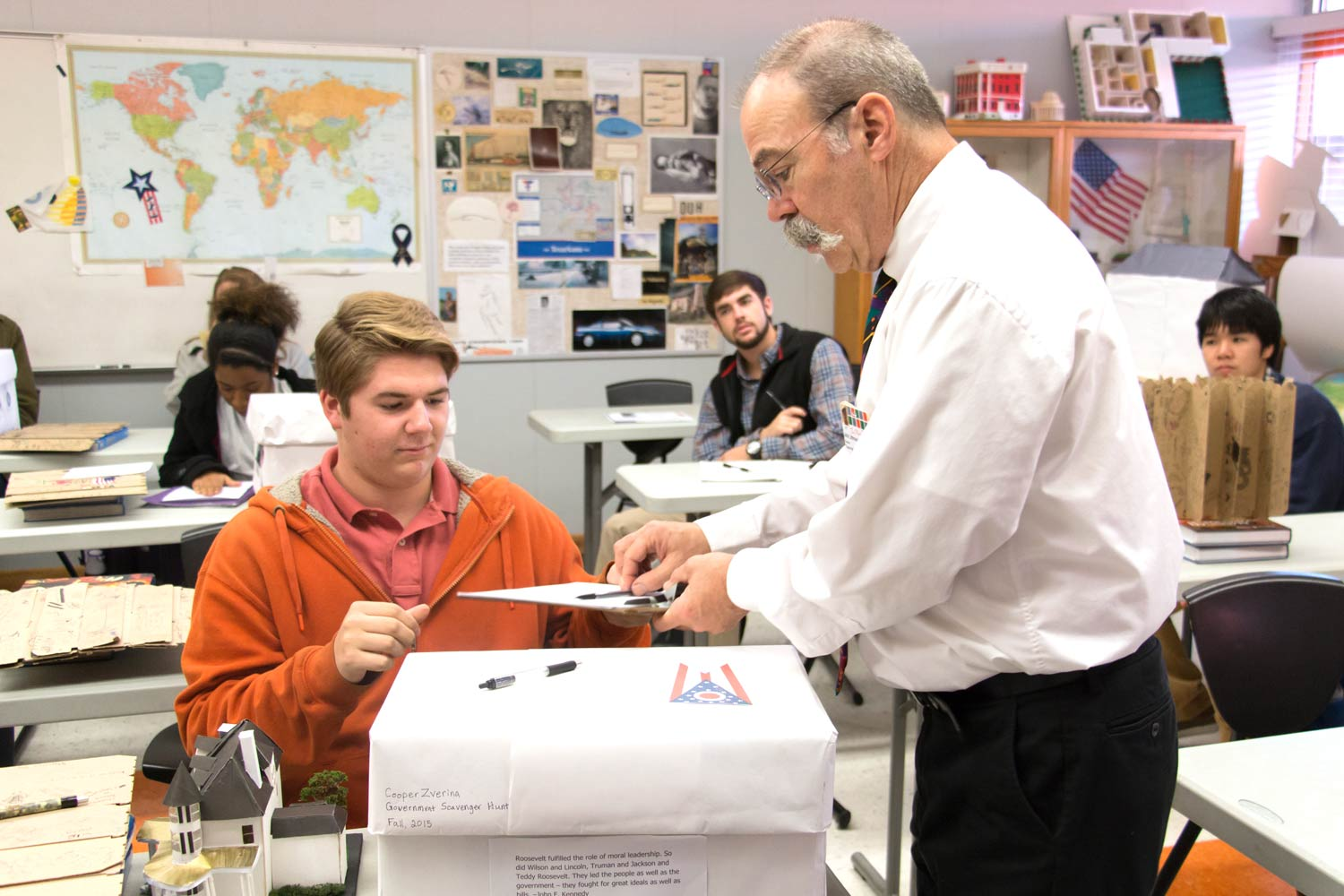2016 graduate Cooper Zverina prepares to show government teacher John Littmann his project. Littmann assigned an annual government scavenger hunt project to his students during his teaching career.