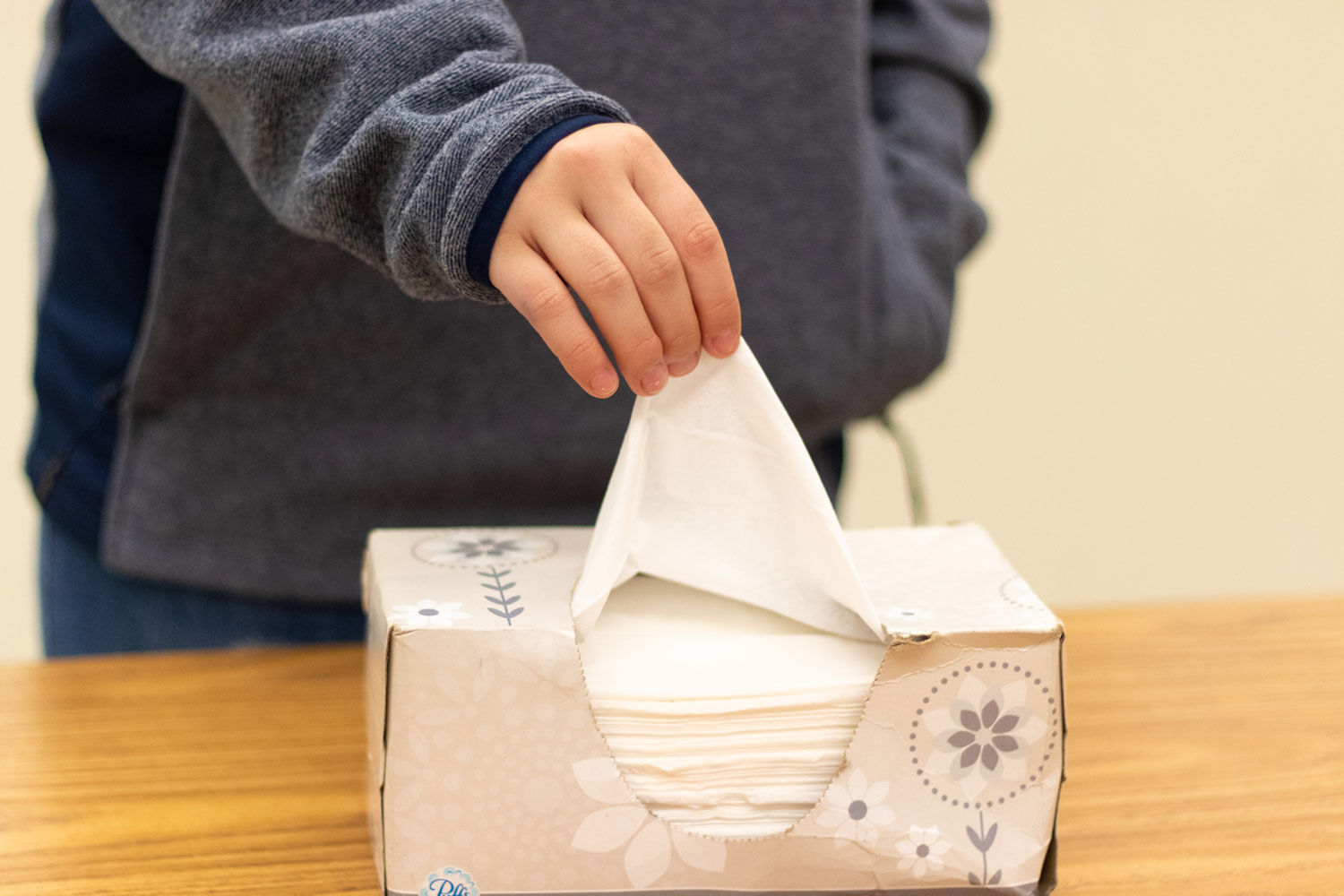 A student grabs a Kleenex after sneezing during the flu season. The recent flu outbreak has caused some schools to close for a few days at a time.