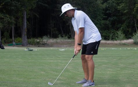 New golf coach Ryan Huntze demonstrates proper stance. Huntze previously worked as Clubhouse Manager for Northridge Country Club.