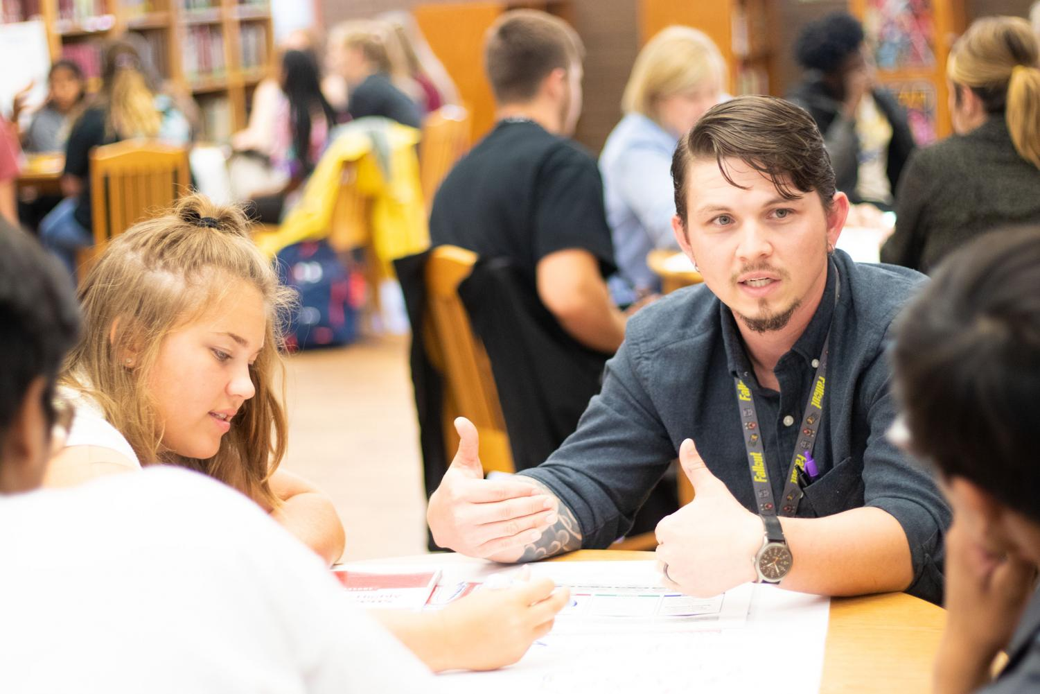 Physics teacher Seth Schrimer discusses Leader in Me with students. Senior Julia Whitehorn implemented the program as a part of her independent research project.