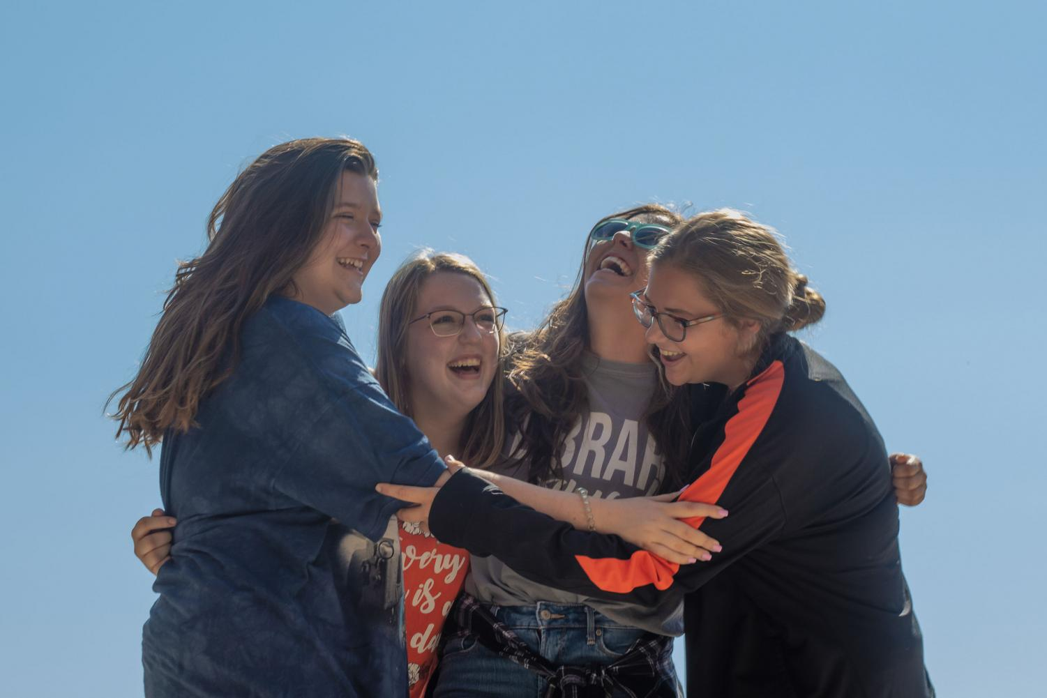 A group of Texarkana teens embrace each other while laughing. They can now hangout without having to worry about doing the same activities.