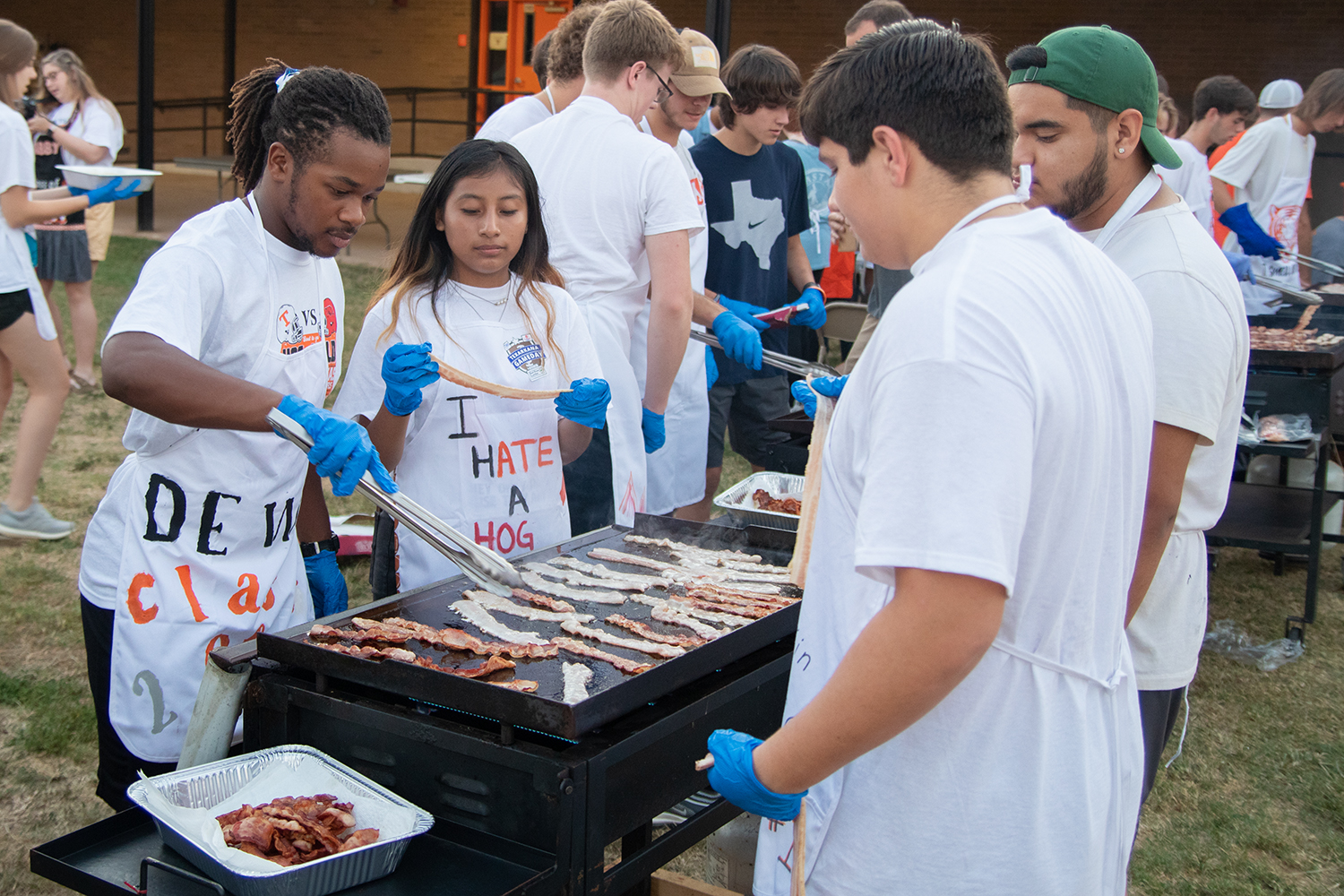 Seniors Dewoine Leeks, Rocioa Gabriel and Mathew Gass cook bacon on a propane griddle at the annual Bacon Fry the morning of the 2019 Texas vs. Arkansas football game. Seniors prepared breakfast for the rest of the student body and community.