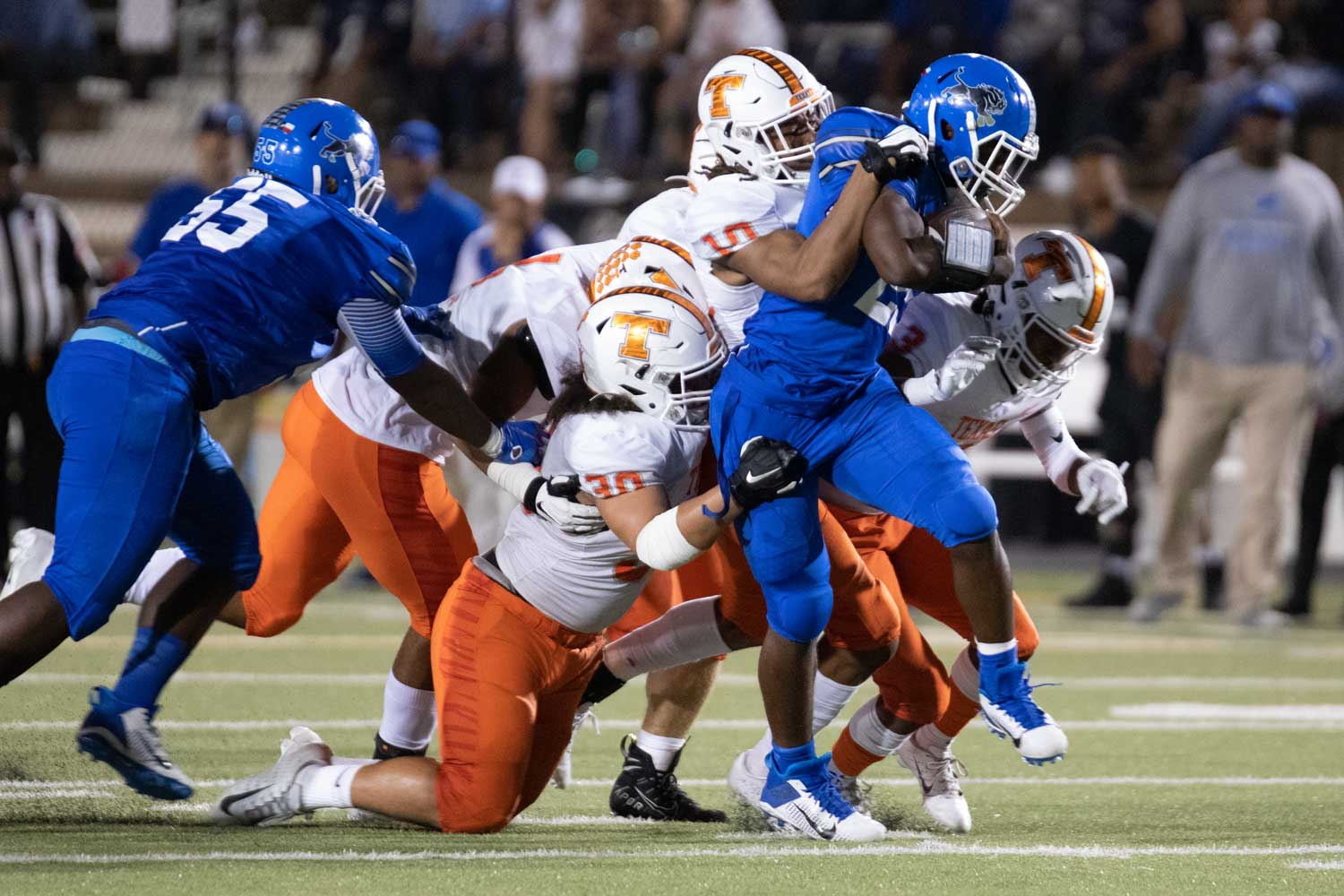 Texas High's defenders Devaughante Jack (30) and Clayton Smith (10) attempt to bring down the running back from John Tyler September 27, 2019. The Tigers lost their district opener 16-0.
