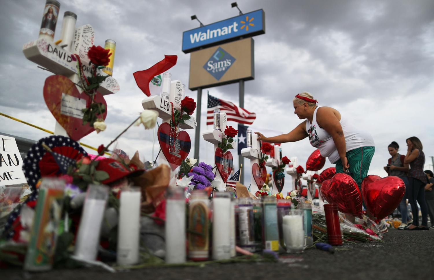 A woman touches a cross at a makeshift memorial for victims outside Walmart, near the scene of a mass shooting which left at least 22 people dead, on August 6, 2019, in El Paso, Texas. Walmart Inc. announced on Tuesday, Sept. 3, 2019m, it will phase out sales of ammunition for handguns and short-barrel rifles. (Mario Tama/Getty Images/TNS)