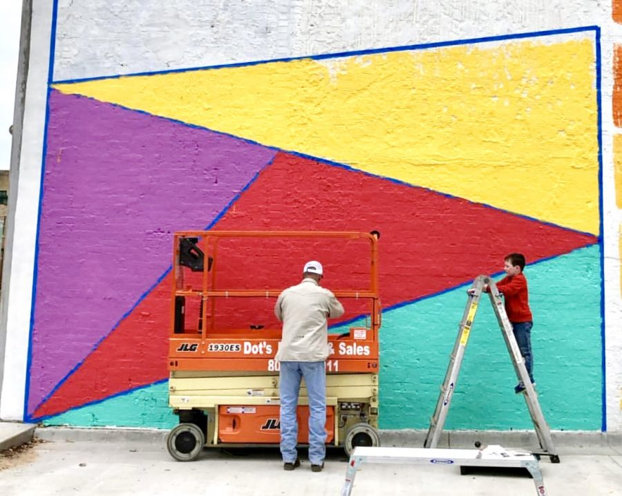 Family+members+help+add+finishing+touches+to+Danielle+Hamblett%27s+mural.+More+murals+are+expected+to+be+painted+downtown+by+the+end+of+the+year.