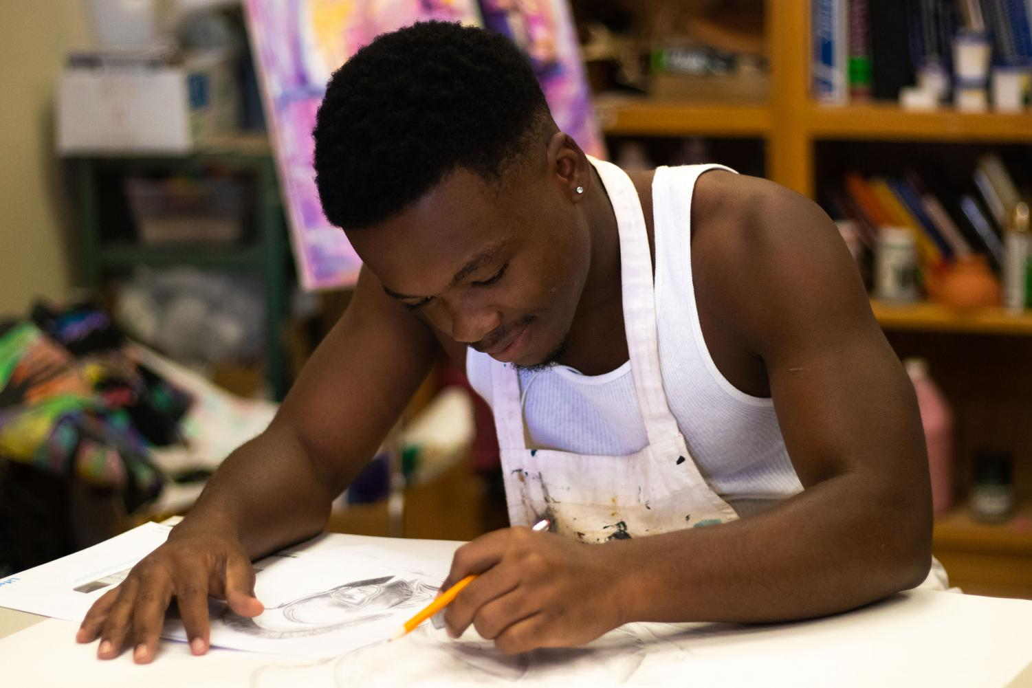 Junior Montrell Denmark works on a new pencil drawing during class. Denmark discovered a way to express how he feels through his art.