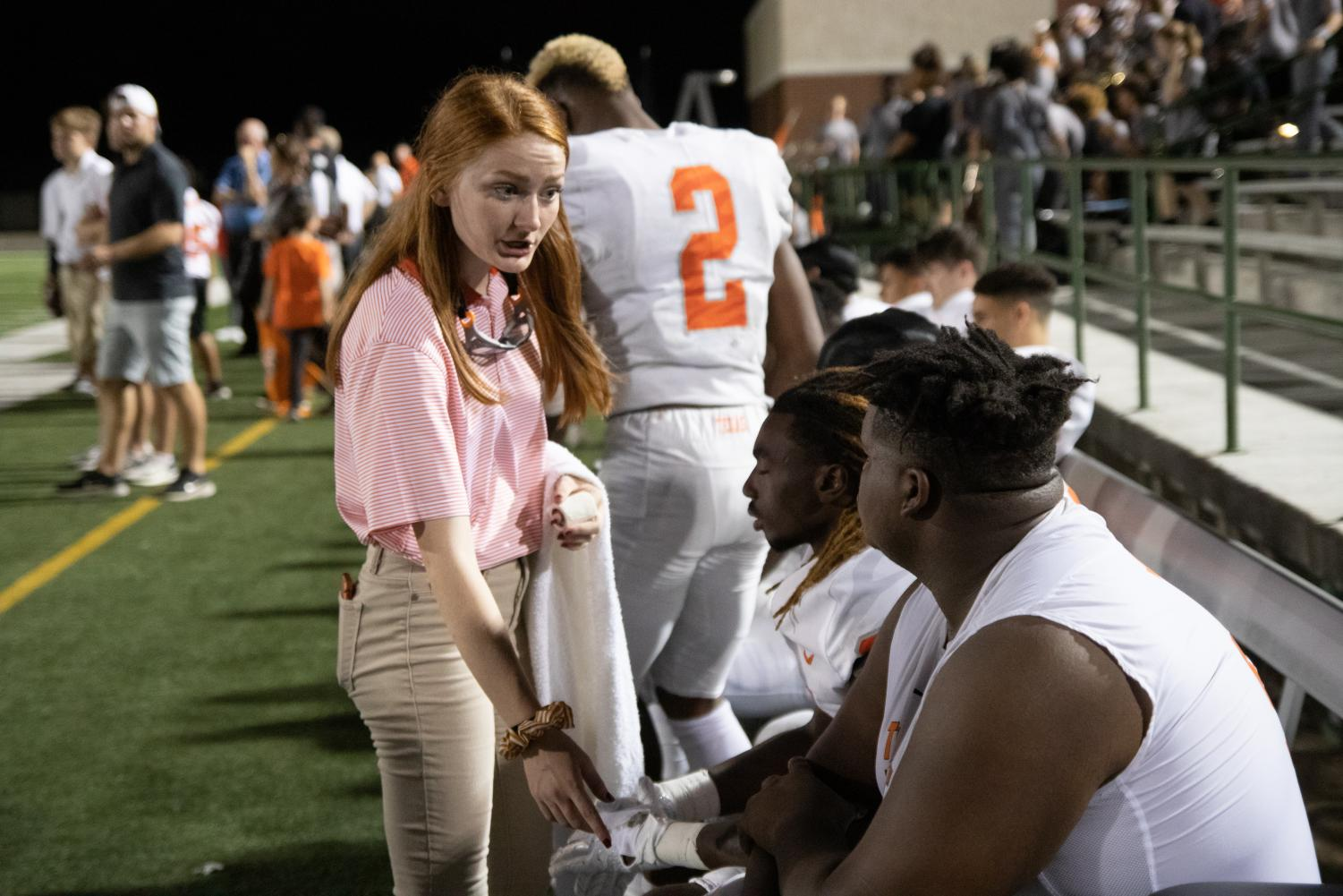 Devun Saveall checks up on a previously injured player at a football game. The student trainers work very hard at sports events to maintain the safety of players.