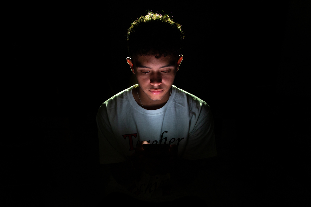 Student enthralled in his phone endures social isolation despite being connected through the internet. Photo illustration