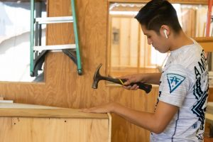 A student in wood shop works on a project in class. Students in courses that prepare them for a trade are given many opportunities that can benefit them in the job field.