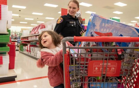 A child swings from a target shopping cart as she shops with a Texarkana police officer at the annual Shop with a Cop and Firefighter. This event allows children to interact with these local heroes in an environment that is not a direct result of an emergency situation.