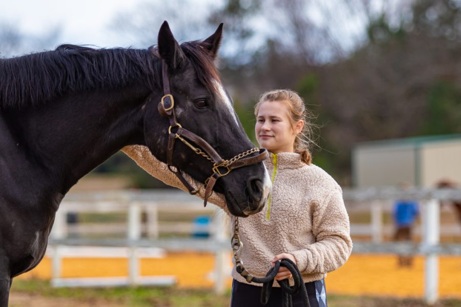 Junior Macy Sloan pets her horse, Jazz. Sloan has participated in competitive dressage events for the past four years.
