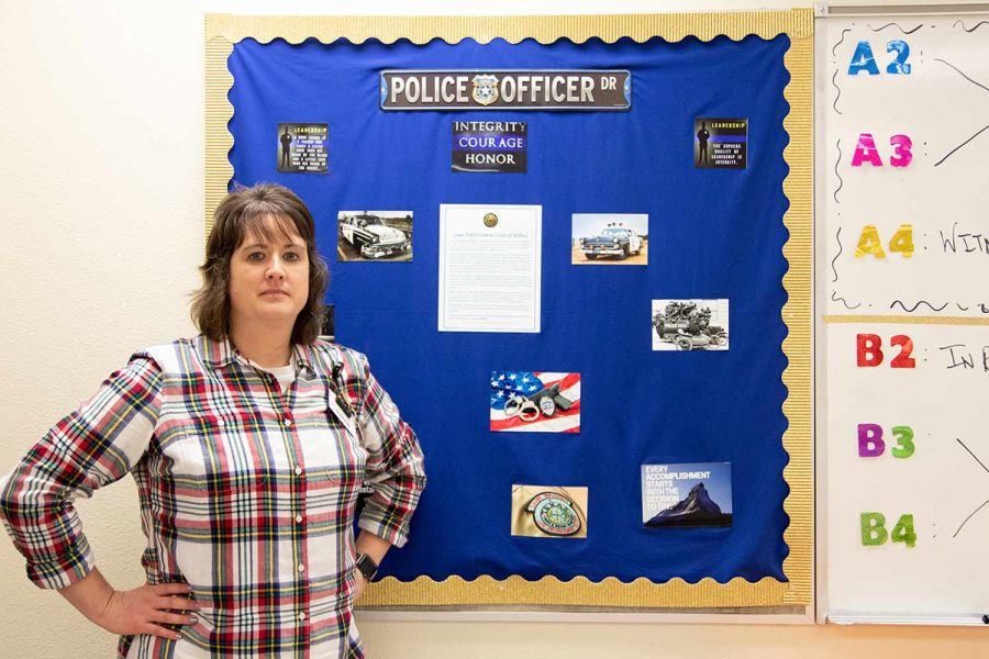 Law enforcement teacher Michelle Shannon stands against a bulletin board in her classroom. Shannon served as a law enforcement officer before becoming a teacher.