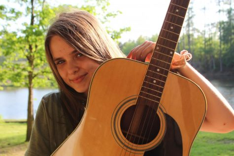 Junior Makenzie Hofert poses with her guitar. She has adopted new hobbies, such as playing instruments, during this time of social distancing.