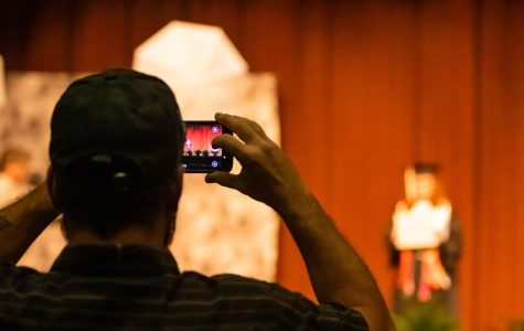 One of the six family members of a graduate snaps a photo while she's on stage. While the situation occurring isn't ideal, families are able to have a more personal experience with one another.