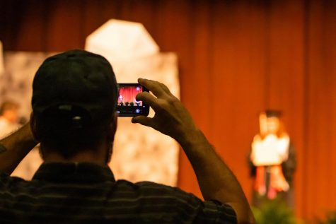 One of the six family members of a graduate snaps a photo while she