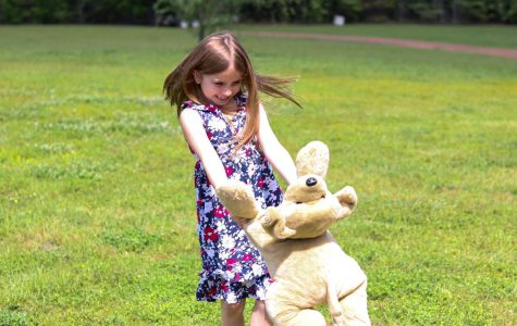 A young girl plays outside with her stuffed bear. Childlike games are often forgotten as people grow and mature.
