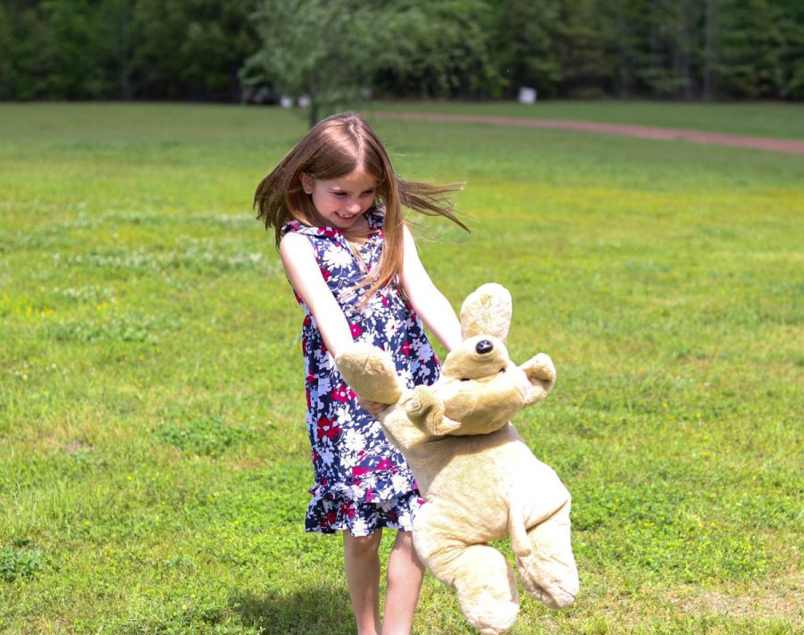A+young+girl+plays+outside+with+her+stuffed+bear.+Childlike+games+are+often+forgotten+as+people+grow+and+mature.