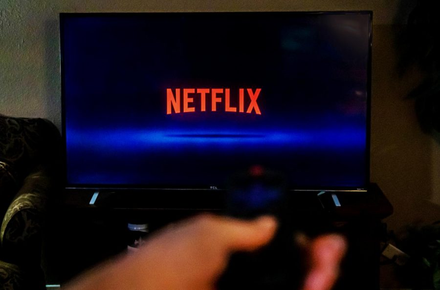 "The word ""Netflix"" overtakes the television screen as a student prepares to find a show to binge."