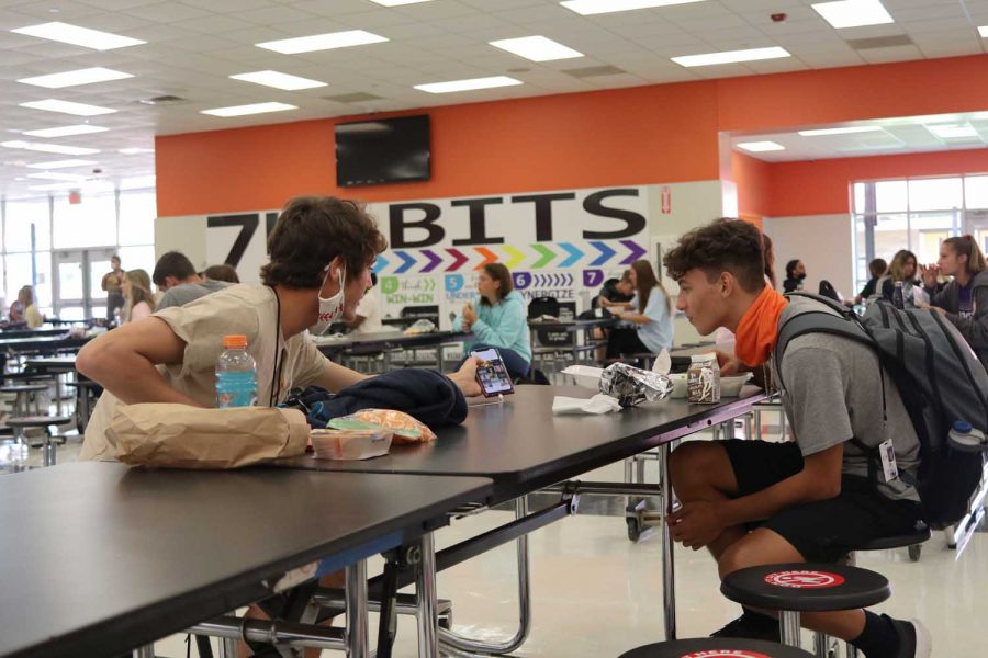 Two unmasked students lean over the table to talk to each other. Despite the spaced out seating, students are still finding a way to break the system.