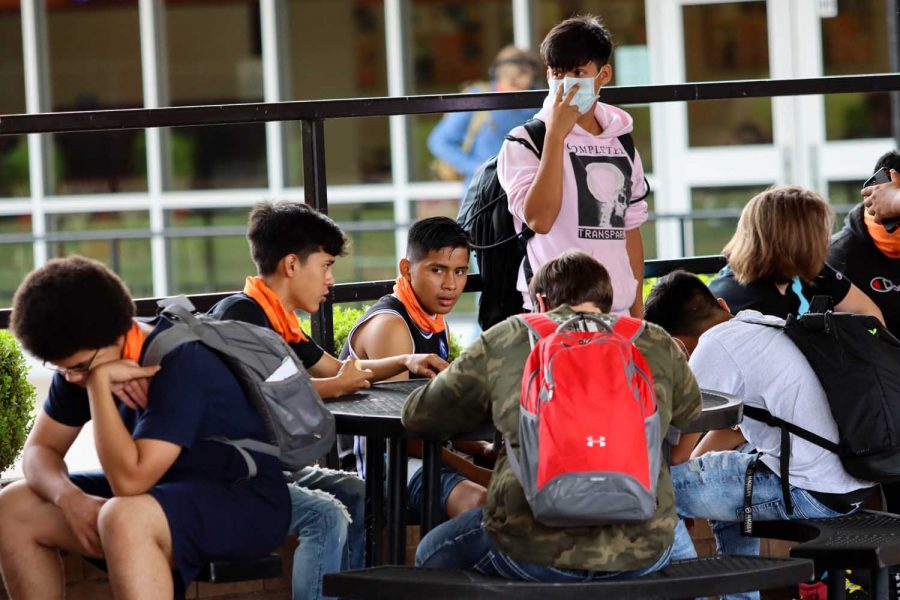 A group of students converses together outside. Lunch is the only time students can be found without their mask on.