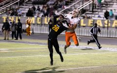 Junior Blake Rogers leaps in the air fighting over the ball with a Mount Pleasant Receiver. The Tigers ended up defeating Mount Pleasant.