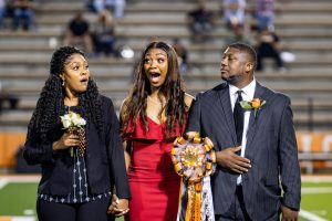 Senior Ashlyn Stiger expresses her shock after hearing her name announced as the homecoming queen. Stiger was escorted onto the field by both of her parents.