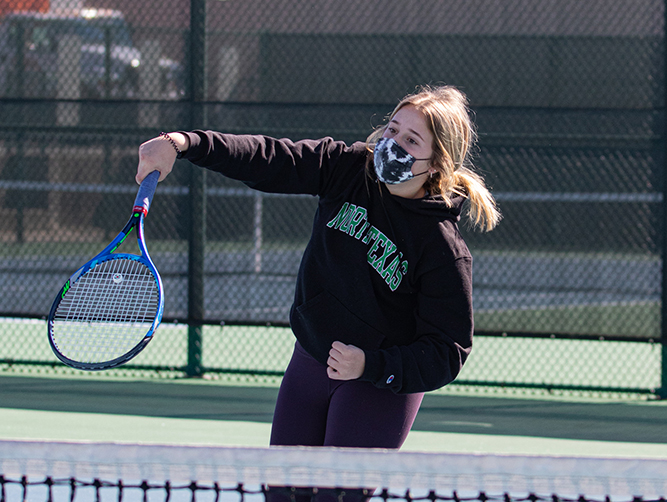 Sophomore Macy Maynard practices tennis while wearing her face mask. Whether people like it or not, masks are required on and off of campus to help prevent the spread of COVID-19.