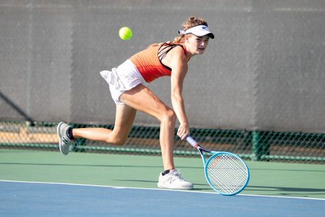 Sophomore Lydia Lee lunges to hit the ball in a match. The tennis team has practiced hard with hopes of making it to state.