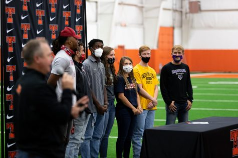 The seven signees of the fall 2020 signing day stand together as Athletic Director Gerry Stanford gives words of motivation to the crowd. Ben Depriest, Trey Lavendar, Graci Henard, Mollie Johnson, Rian Cellers, Jackson Halter and Clayton Smith all committed to their colleges on Nov. 11.