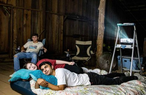 A group of friends gathers in an old barn to watch a classic horror film on a projector. This year, teenagers celebrated Halloween in numerous creative ways due to COVID-19 restrictions.