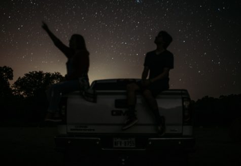 Two teens sit on the bed of a truck while star gazing. Zodiac signs play an important role in many  peoples