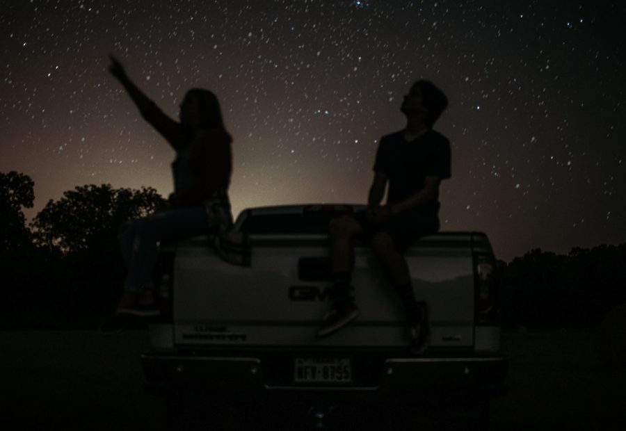 Two teens sit on the bed of a truck while star gazing. Zodiac signs play an important role in many  peoples' lives.