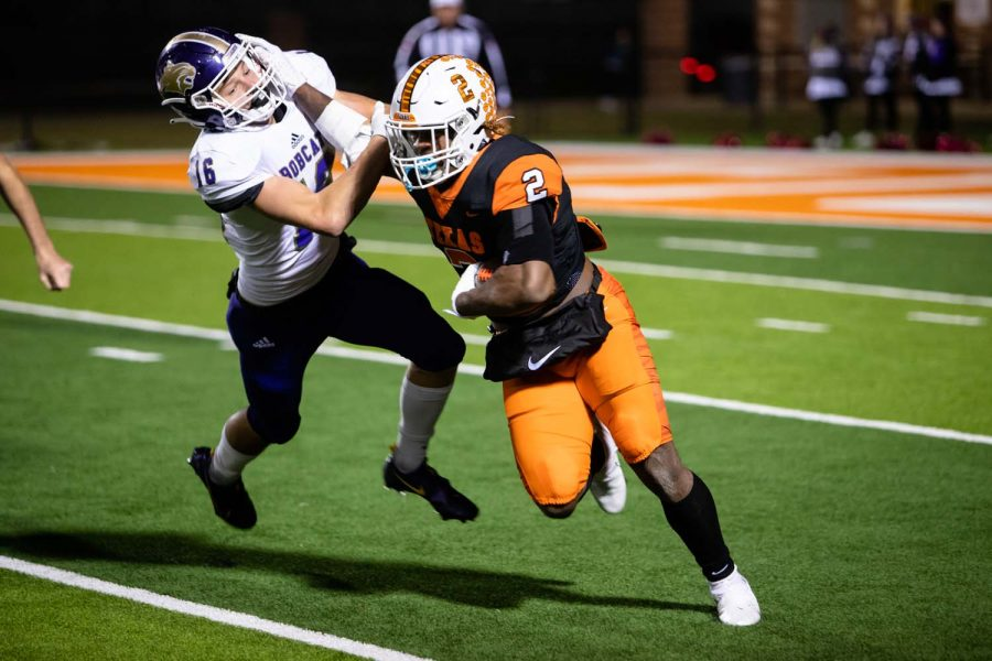 Junior Braylon Stewart stiff arms a Hallsville defender in attempt to gain yards for the Tigers. The Tigers won with a score of 56-17.