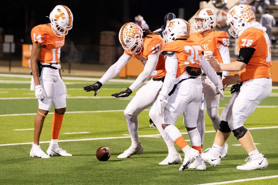 Senior Clayton Smith signals for his teamates to stay away from the ball as a punt rolls a few more inches. The Texas High Tigers won thier final district game against Whitehouse by a score of 51-21, leaving them undefeated for the season.