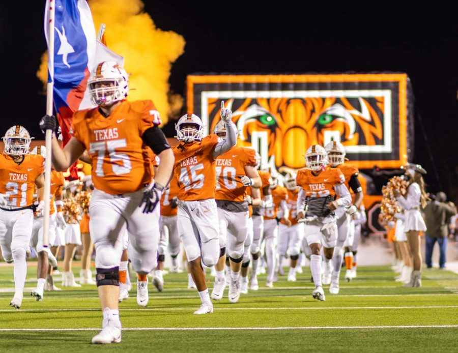 The Texas High Tigers storm the field before kickoff. Texas High played against Whitehouse at Tiger Stadium at Grim Park.