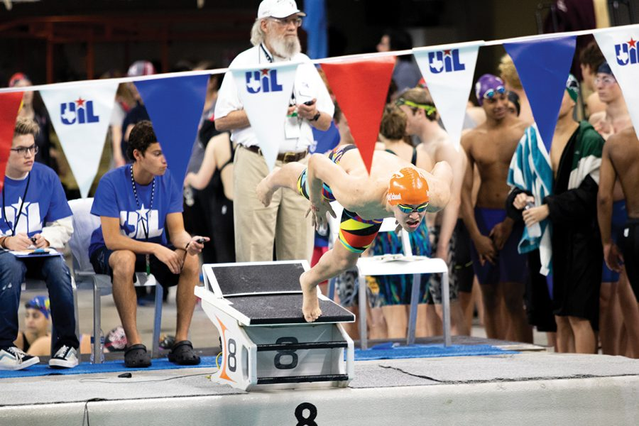Senior Logan Diggs dives into the pool during one of his swim meets. This year, due to COVID-19, the swimmer's family is not permitted to attend away meets.