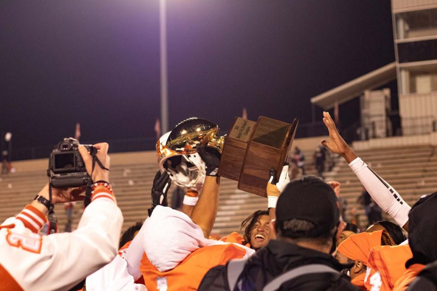 The Texas High Tigers raise up the District Championship trophy in triumph after their victory against the Whitehouse Wildcats.