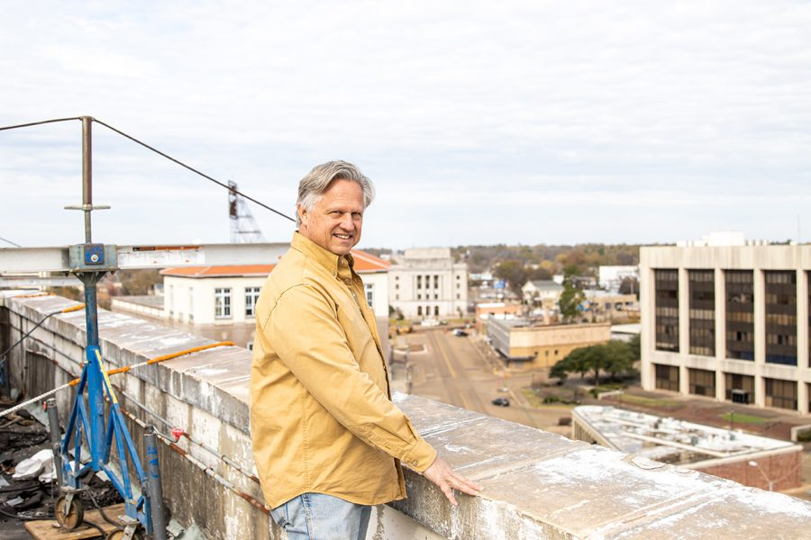 David Peavy poses while standing atop the roof of the Texarkana National Bank. The currently abandoned bank will soon be remodeled into apartment complexes.