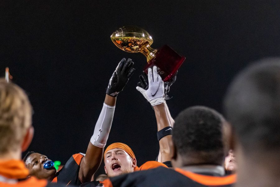 Senior Colin Shelley waves the play-offs trophy in the air after Texas High won the game against Lake Creek. The first play-offs game took place in Nacogdoches.