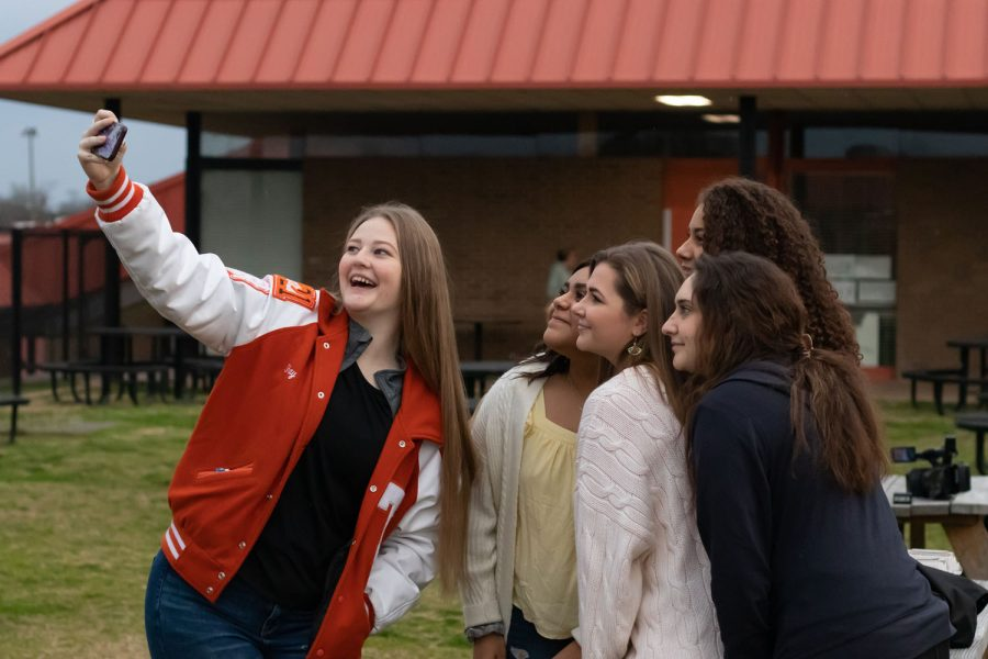 Senior Shailee Poole takes a selfie with her friends at today's bacon fry. People took numerous pictures at the event for memories.