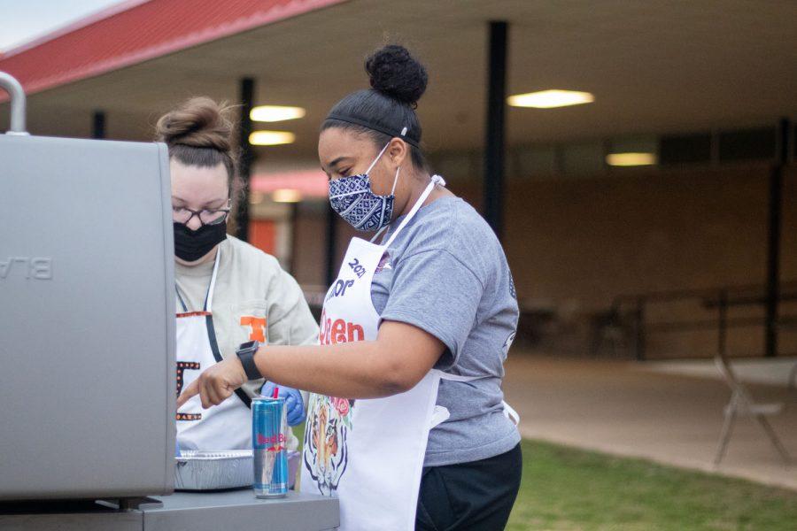 Senior, Taylor Bayonne, helps faculty cook bacon, as she enjoys bacon fry, one of her last senior memories.