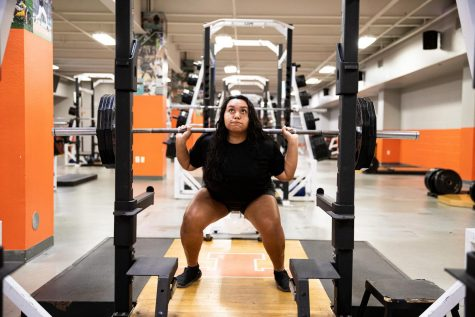 Senior Mariza Paez practices in the weight room with the girl