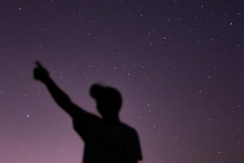 A senior points at his constellation during a starry night. There