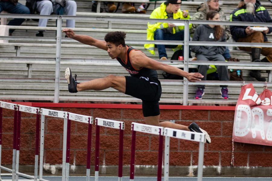 Senior Caden Miller glides over a hurdle in the 100m race. Miller competes in both hurdles and relay races.
