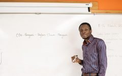 Mayowa Onare writes his name on the white board in his classroom. Despite Onare's full name, he goes by Abraham.
