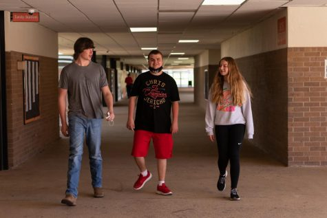 Junior Nicholas Price strolls the halls with friends, junior Thompson Matteson and freshman Annabeth Grace Killian. Although he is kind to others, Autism sometimes hinders his social skills.