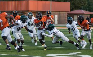 Running Back Braylon Stewart attempts to dodge the Lobos. A scrimmage was held at the Grim stadium on August 20, 2021.