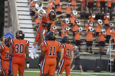 Senior quarterback Brayson McHenry is lifted by teammate senior Qushawn McCulloch after scoring a touchdown against the Tyler High Lions. The Tigers held onto the lead and ended their season opener 24-10 Friday night at Tiger Stadium.