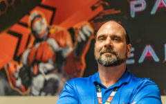 Allen stands in front of artwork in the Esports room designed by Brian Jones.