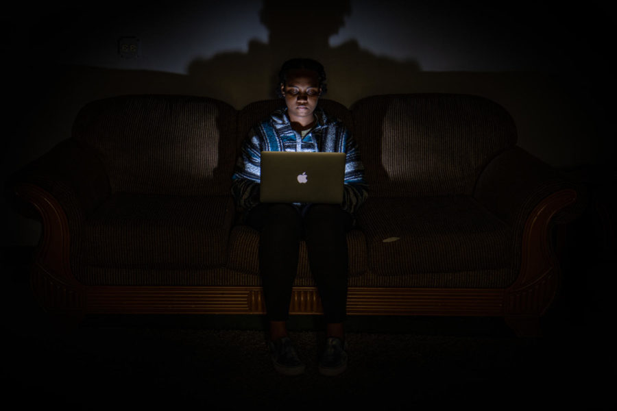 A student works on a laptop during school in the dark. Many people this year are readjusting to the in-person learning environment.